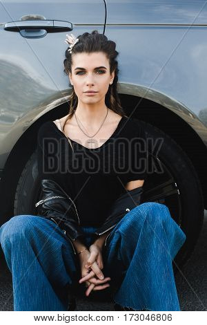 Horizontal outdoors portrait of young woman sitting at the vehicle wheel and looking away.