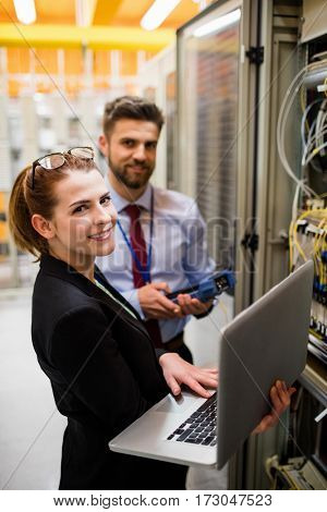 Portrait of technicians using laptop while analyzing server in server room