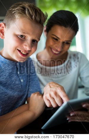 Mother and son using digital tablet in the living room at home