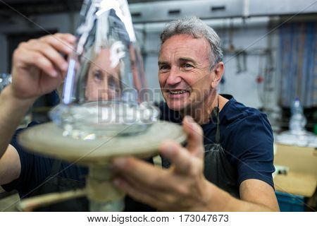 Glassblower and a colleague examining glassware at glassblowing factory
