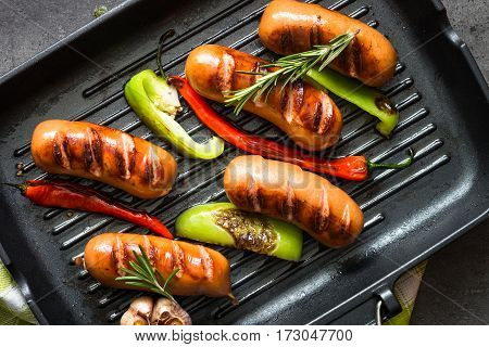 Fried sausages with herbs and vegetables in grill pan at black background. Top view copy space.
