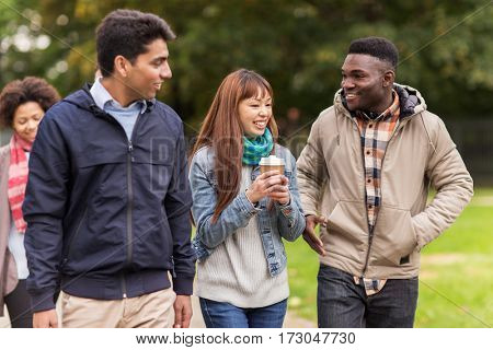 people, friendship, communication and international concept - group of happy friends walking along autumn park and drinking coffee