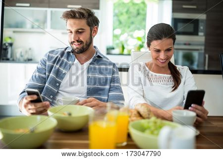 Couple using mobile phone while having breakfast at home