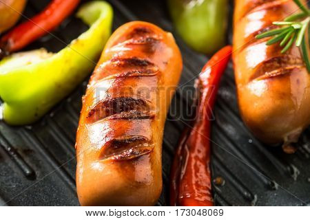 Fried sausages with herbs and vegetables in grill pan at black background.