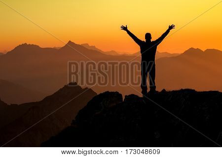 Happy celebrating winning success man at sunset or sunrise standing elated with arms raised up above his head in celebration of having reached mountain top summit goal during hiking travel trek. Tirol, Austria. Bavaria.