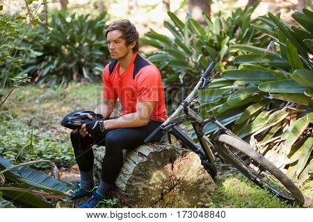 Exhausted male mountain biker relaxing on a tree trunk in the forest