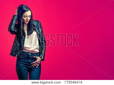 Brooding stylish girl with black hair in a leather jacket and blue jeans on a bright pink background.