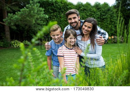 Portrait of happy family standing on grass in park on a sunny day