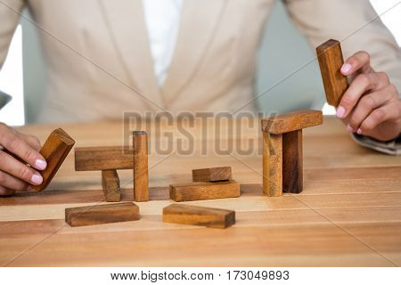 Business man placing wooden block on a tower in office