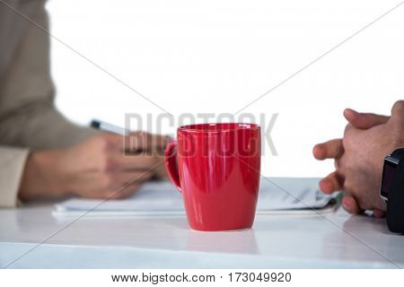 Businesswomen writing on clipboard with coffee mug on desk against white background