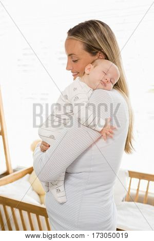 Mother holding and embracing her baby boy at home