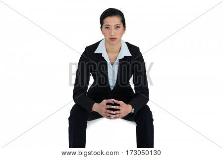 Portrait of confidence businesswoman sitting against white background