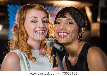 Portrait of female friends singing together in bar