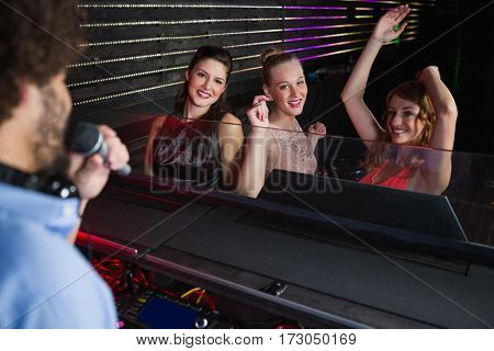 Male disc jockey playing music with three women dancing on the dance floor at bar
