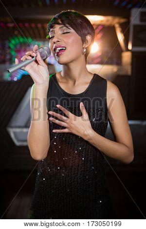 Beautiful woman singing in bar