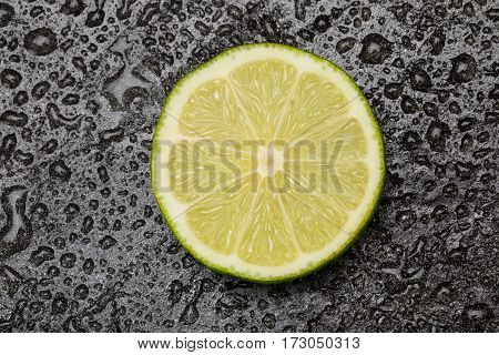 close up view of fresh lime slice on black