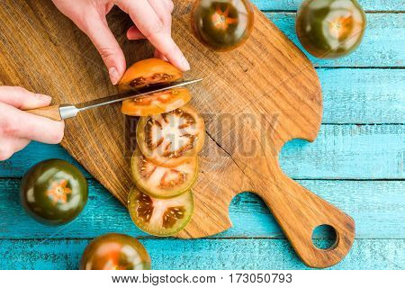 top view of hands cutting fresh tomatoes on cutting board