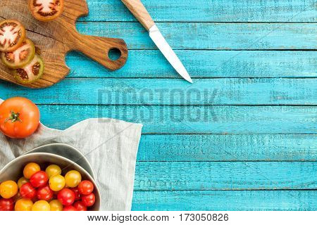 top view of various fresh tomatoes in bowl and cutting board