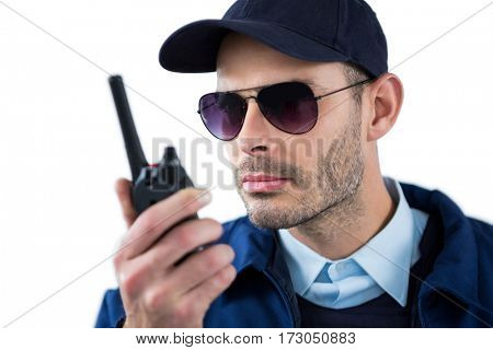 Handsome security officer talking on walkie-talkie against white background