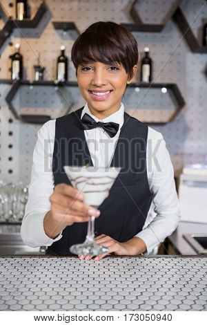 Portrait of smiling waitress holding glass of cocktail in counter at bar