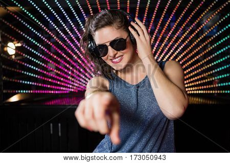 Pretty female DJ playing music at nightclub