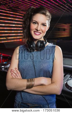 Portrait of pretty female DJ standing with arms crossed at night club