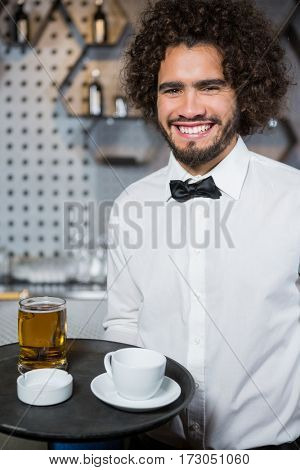 Portrait of smiling waiter holding tray of beer glass and tea cup in bar