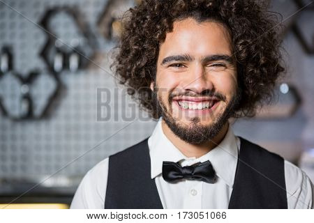 Portrait of smiling bartender standing in bar counter