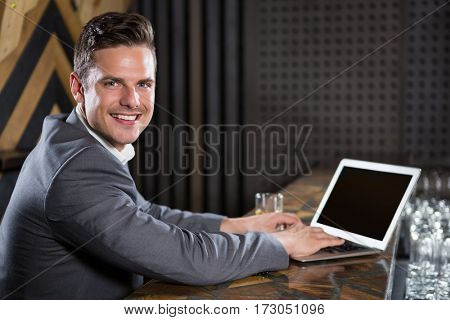 Portrait of man using laptop in bar counter at bar