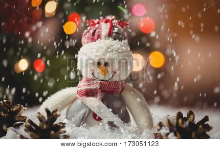 Snowman and pine cone on snow during christmas time