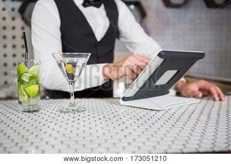 Bartender using digital tablet at bar counter in bar