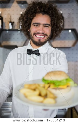 Portrait of smiling waiter serving plates of potato chip and burger in bar