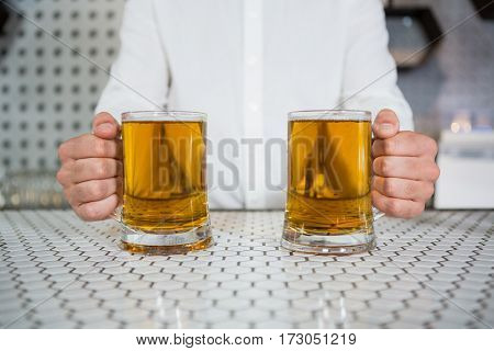 Mid section of bartender holding two glass of beer in bar counter at bar