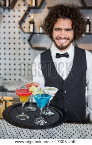 Portrait of bartender holding tray of cocktails and milkshake in bar