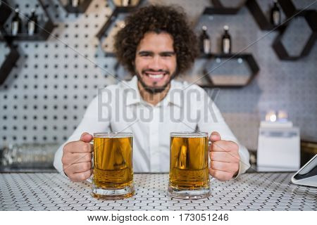 Portrait of smiling bartender holding two glass of beer in bar counter at bar