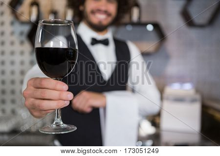 Portrait of smiling bartender serving glass of red wine in bar counter at bar