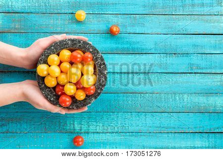 top view of hands holding cherry-tomatoes in bowl on table