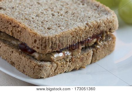 Sandwich made with two slices of wholegrain bread and jam and peanut butter