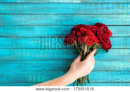 Top view of hand holding roses bouquet with copy space