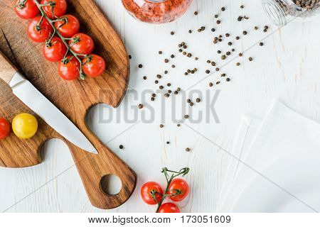 Top view of fresh ripe tomatoes and knife on cutting board and peppercorns on table