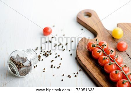 Close-up view of fresh tasty tomatoes on cutting board and peppercorns on wooden table