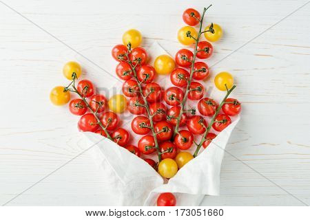 Top view of fresh ripe cherry tomatoes wrapped in white cloth
