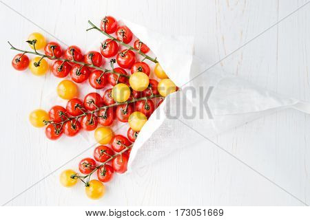 Top view of fresh ripe red and yellow tomatoes wrapped in white napkin