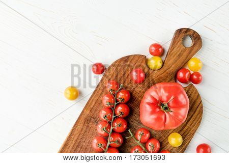 Top view of fresh red and yellow tomatoes on wooden cutting board