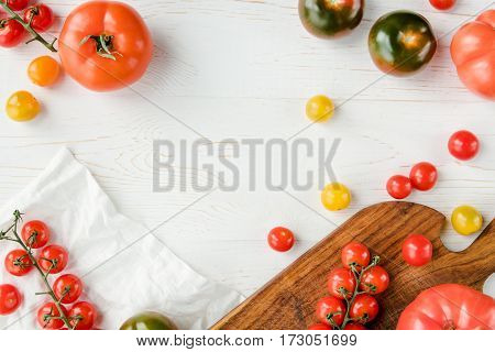 Top view of various fresh tomatoes on cutting board white cloth and table