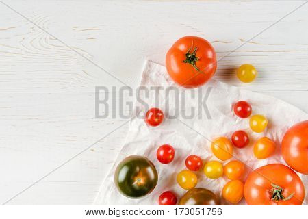 Top view of various fresh ripe tomatoes on wooden table and white cloth
