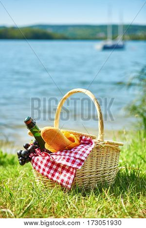 Picnic Basket With Food Near The Water