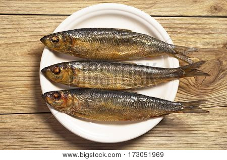 Smoked herring in white plate on old wooden table top view