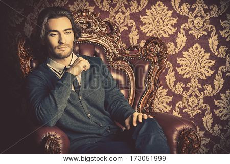 Fashionable male model in elegant classical clothes posing in apartments with classical vintage interior.