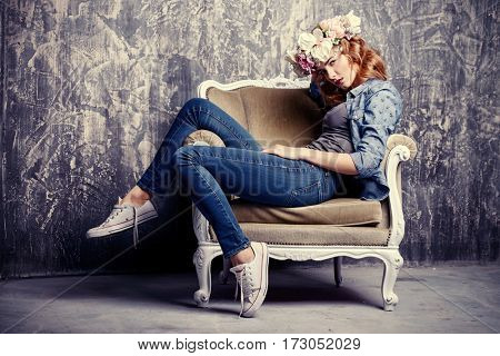 Sexy young woman wearing casual jeans clothes and wreath of flowers posing in vintage armchair. Cosmetics and make-up. Spring and summer fashion.